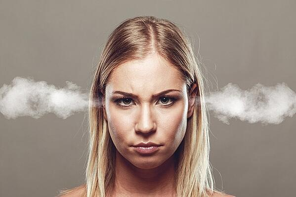 A blonde woman facing camera with smoke coming out of her ears.jpg