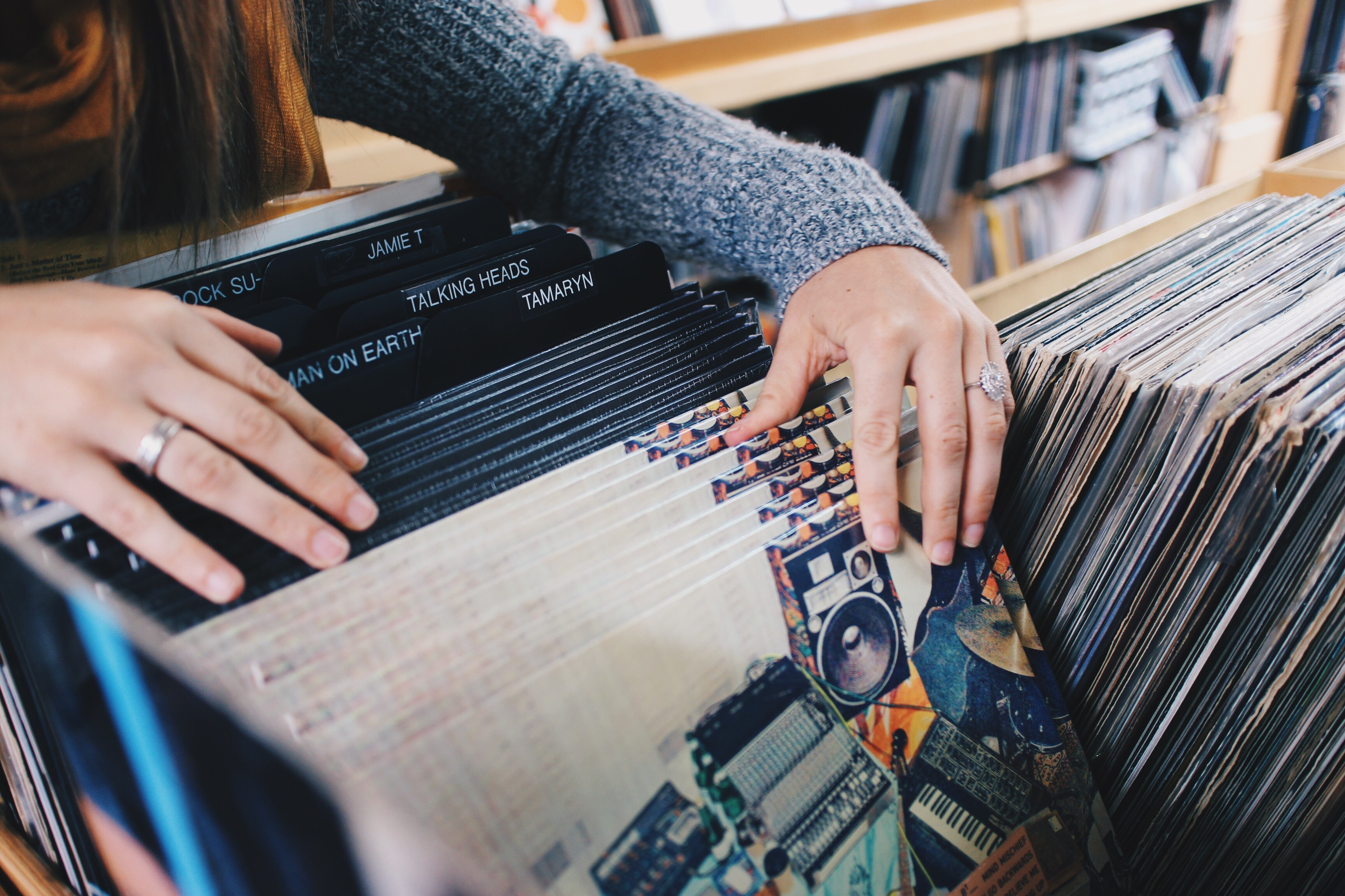 A person sorts through vinyl records at a record store.jpg