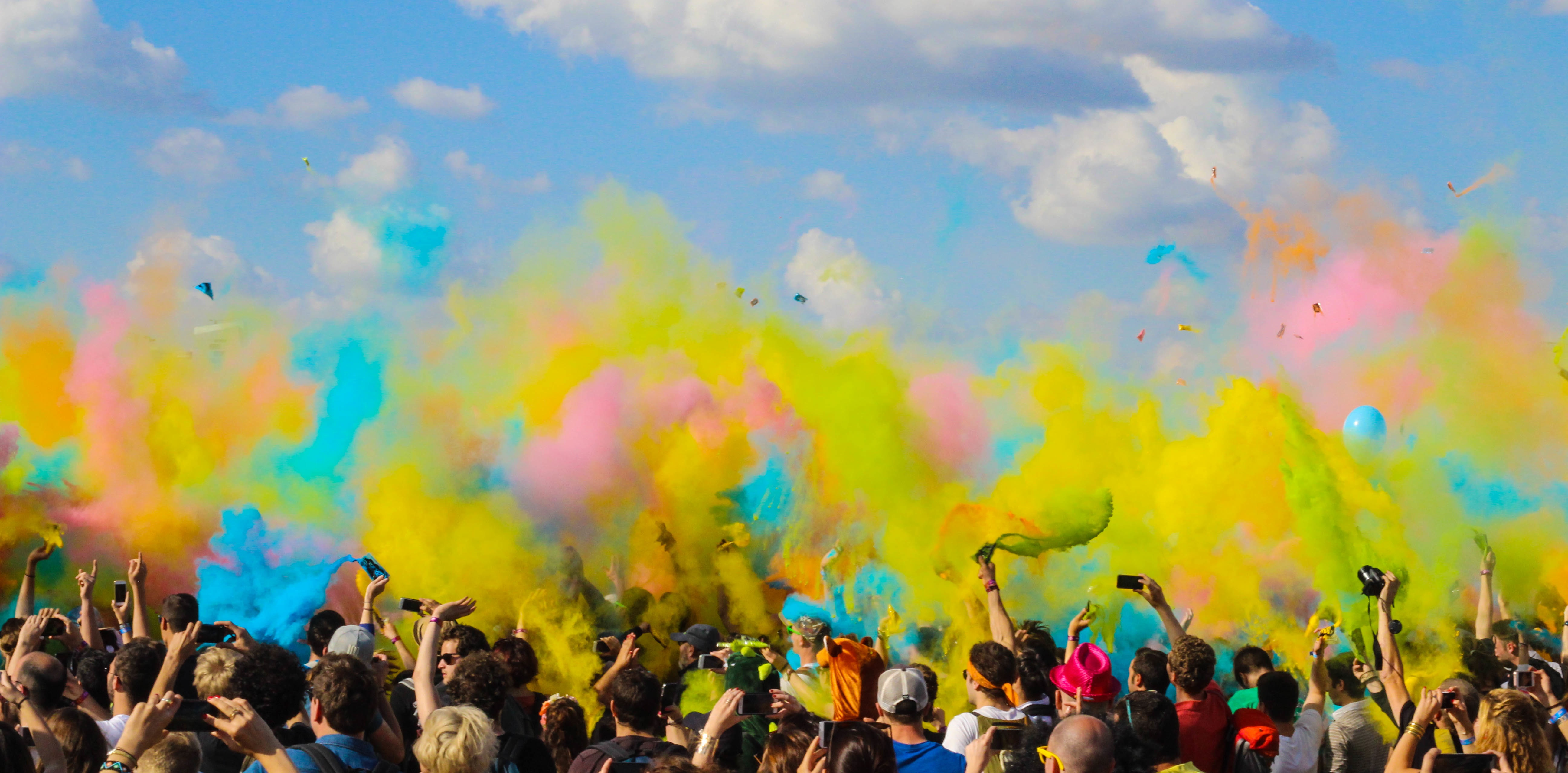 A_crowd_at_a_concert_with_colorful_smoke_bombs_floating_above_them.jpg