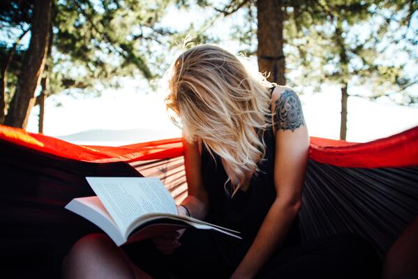 A_woman_reads_a_book_on_outdoors