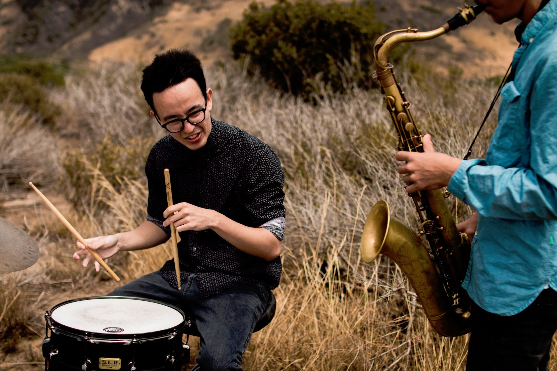 In a field outdoors person wearing glasses drums on the left and someone plays saxaphone on the righ.jpg
