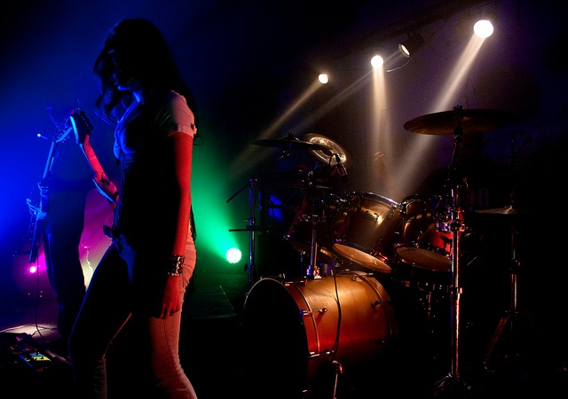 A musician stands onstage in front of a drum kit at a concert.