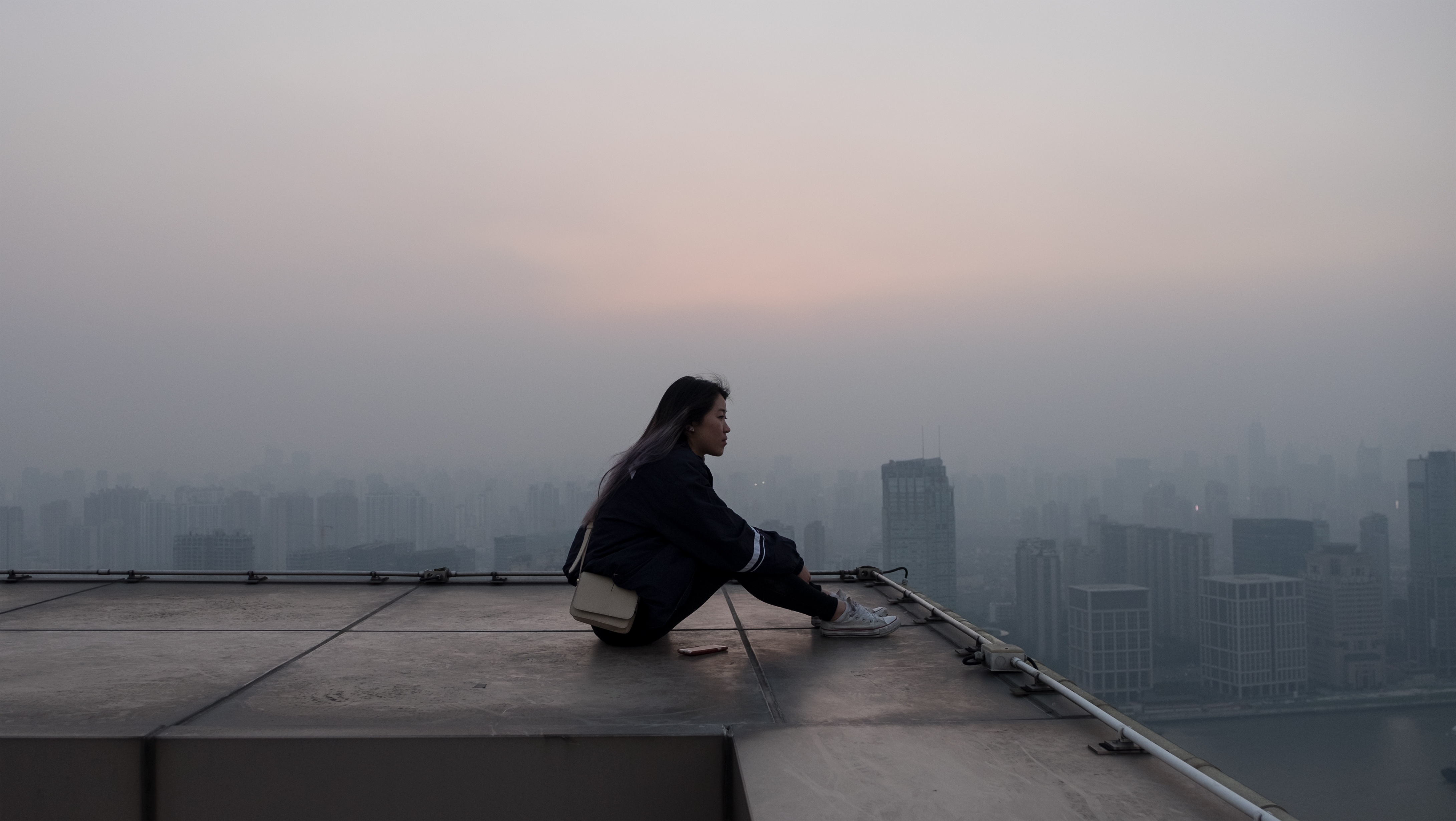 person sitting on rooftop with skyline in view.jpg