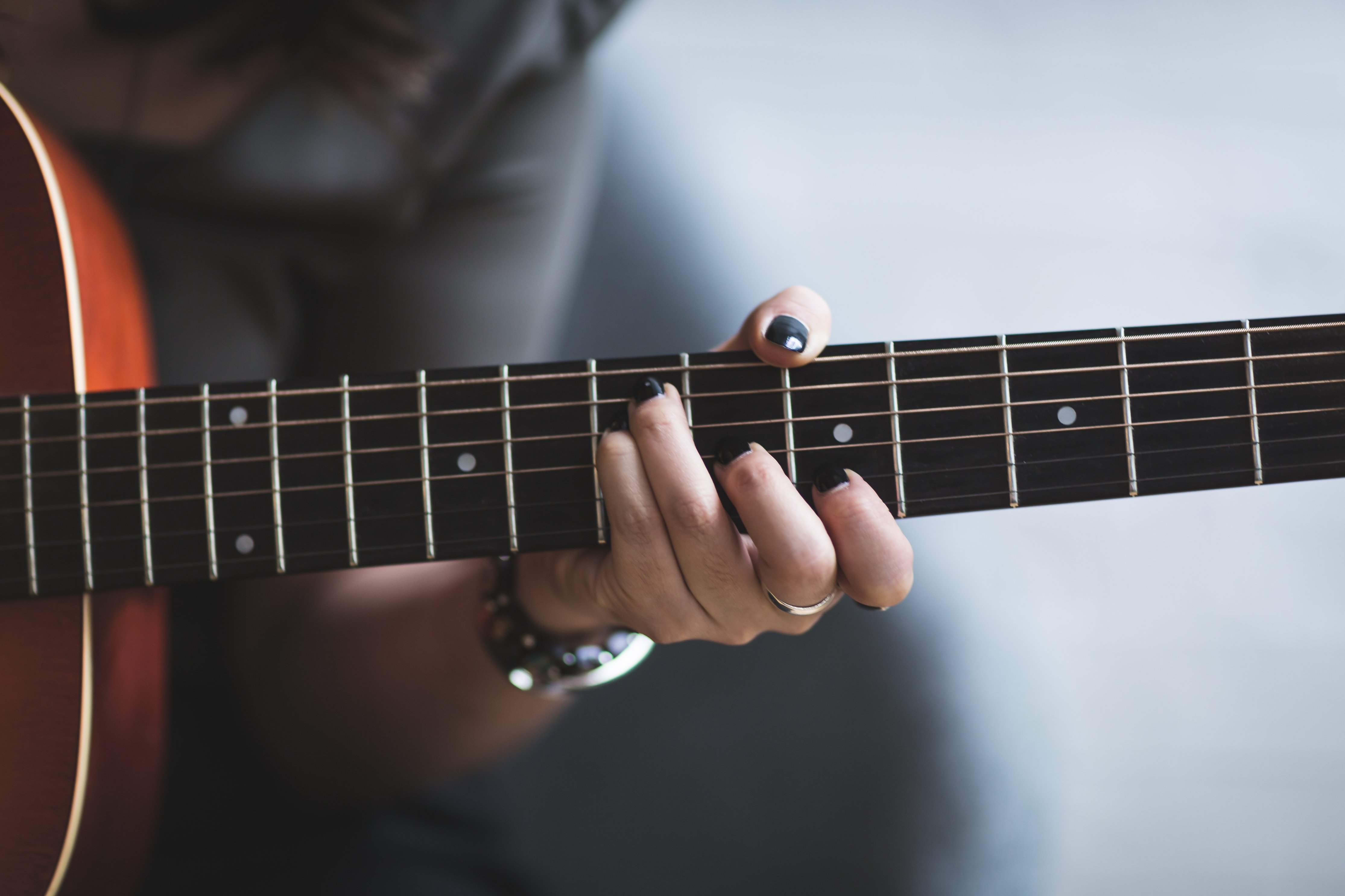 person with painted black nails plays guitar.jpg