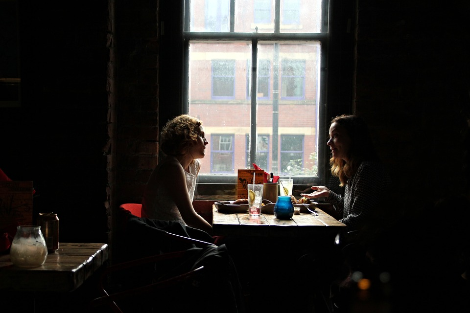 two_women_having_a_conversation_in_a_restaurant.jpg