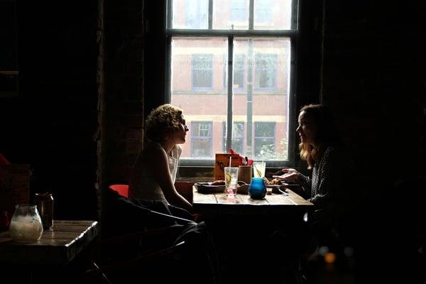 two_women_having_a_conversation_in_a_restaurant.jpg